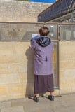 Mulher que reza fora da parede lamentando Fotografia de Stock Royalty Free