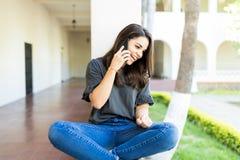 Mulher que ri durante a conversação de telefone celular no terreno foto de stock