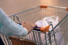 Mulher que rola um carro em um supermercado fotografia de stock royalty free