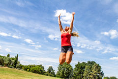 A mulher que salta altamente para alcançar o céu no parque verde Imagens de Stock Royalty Free