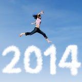 A mulher que salta com ano novo 2014 de nuvens Fotos de Stock Royalty Free