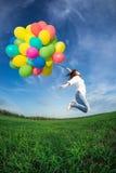 A mulher que salta com balões do brinquedo Fotos de Stock Royalty Free