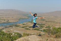 A mulher que salta com felicidade e alegria imagens de stock