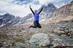 A mulher que salta de uma rocha nos cumes montanhosos italianos fotos de stock royalty free