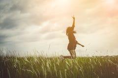 A mulher que salta e que aumenta acima seus mão e dedo dois sobre a grama Imagens de Stock