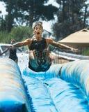 A mulher que salta e que prepara-se para ir abaixo de uma corrediça Foto de Stock