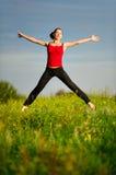 A mulher que salta em um por do sol Fotografia de Stock