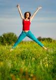 A mulher que salta em um por do sol Imagens de Stock Royalty Free