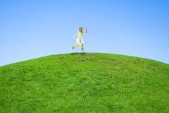 A mulher que salta em um prado verde Fotos de Stock Royalty Free