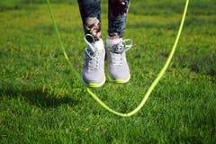 a mulher que salta em uma corda de salto no parque foto de stock