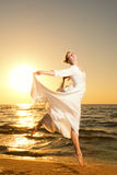 A mulher que salta em uma praia Imagens de Stock
