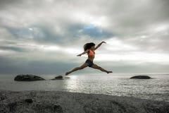 A mulher que salta em uma rocha no por do sol na praia de Bakovern, Cape Town Fotografia de Stock