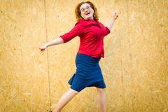 A mulher que salta na frente da cerca dos painéis de madeira do mdf foto de stock