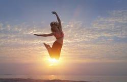 A mulher que salta na praia Fotografia de Stock