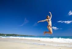 A mulher que salta na praia imagem de stock royalty free