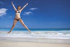 A mulher que salta na praia imagens de stock royalty free
