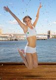 A mulher que salta no ar contra a água e a skyline e os confetes foto de stock