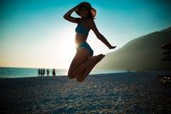 A mulher que salta no ar na praia tropical, tendo o divertimento e comemorando o verão, mulher brincalhão bonita no salto branco  Fotografia de Stock