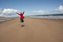 A mulher que salta para a alegria Fotos de Stock Royalty Free