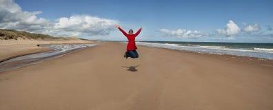 A mulher que salta para a alegria Imagem de Stock