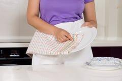 Mulher que seca os pratos na cozinha foto de stock royalty free
