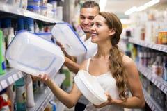 Mulher que seleciona baldes na loja Fotos de Stock