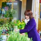 Mulher que seleciona flores frescas no mercado parisiense Fotografia de Stock