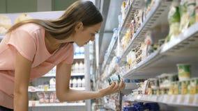 Mulher que seleciona produtos láteos no refrigerador no departamento do mantimento do shopping imagem de stock