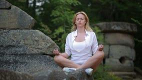 Mulher que senta e que medita sobre o dólmem de pedra vídeos de arquivo