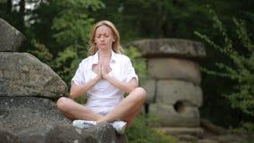 Mulher que senta e que medita sobre o dólmem de pedra filme