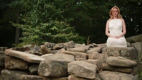 Mulher que senta e que medita sobre o dólmem de pedra video estoque