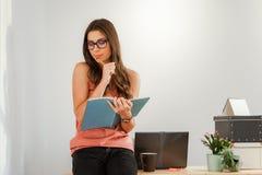 Mulher que senta em casa a mesa com um caderno Imagem de Stock