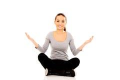 Mulher que senta equipado com pernas transversal com mãos abertas Foto de Stock Royalty Free