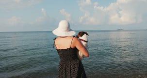 Mulher que senta-se além de seu Jack Russell no cais que olha ao mar filme