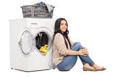Mulher que senta-se ao lado de uma máquina de lavar foto de stock royalty free