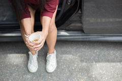 Mulher que senta-se ao lado do carro e que guarda a xícara de café descartável Fotos de Stock