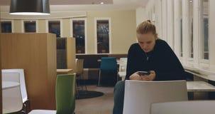 Mulher que senta-se apenas no café e que usa o móbil video estoque