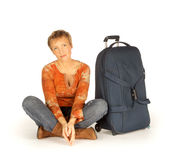 Mulher que senta-se com a mala de viagem no branco Fotografia de Stock
