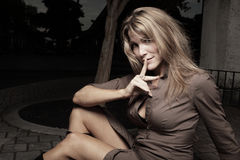 Mulher que senta-se com o dedo nos bordos Imagens de Stock Royalty Free