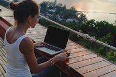 Mulher que senta-se com um portátil e uma xícara de café na frente da opinião do por do sol imagem de stock royalty free