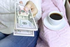 Mulher que senta-se com uma xícara de café e que guarda um bloco de cinqüênta notas de dólar imagens de stock