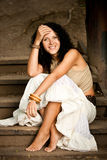 Mulher que senta-se em escadas de madeira Imagens de Stock Royalty Free