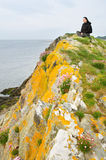 Mulher que senta-se em penhascos do mar Imagem de Stock Royalty Free