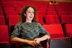 Mulher que senta-se em poltronas no cinema Imagem de Stock