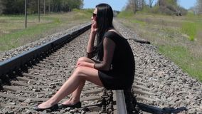 Mulher que senta-se em railway e que fala no telefone esperto filme