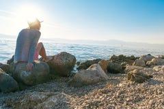 Mulher que senta-se em rochas pelo mar imagem de stock royalty free