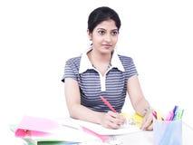 Mulher que senta-se em sua mesa de escritório Imagem de Stock Royalty Free