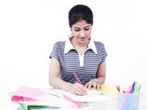 Mulher que senta-se em sua mesa de escritório Fotos de Stock
