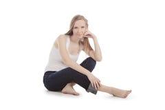Mulher que senta-se em um assoalho branco com os pés descalços fotografia de stock royalty free
