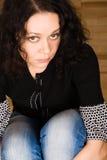 Mulher que senta-se em um assoalho de madeira imagens de stock